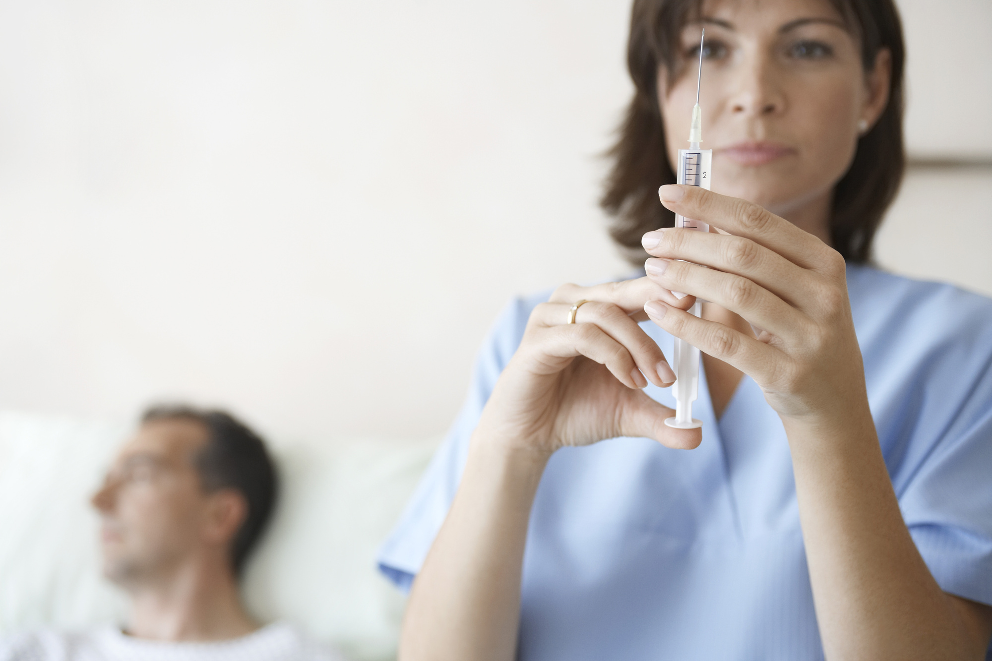Blurred nurse preparing syringe for Injection by male patient in bed